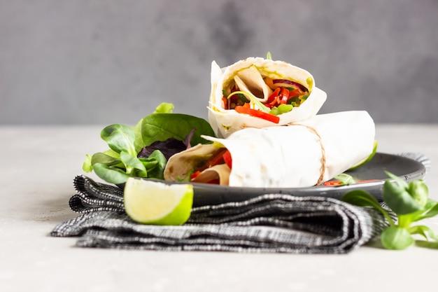 Tortilla wraps sandwichs salade de légumes servie avec un mélange de salade, citron vert et piment