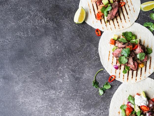 Tortillas aux légumes et tranches de steak de boeuf. avocats, tomates, oignons rouges et rencontre avec la coriandre et le jus de citron vert dans les tortillas. nourriture mexicaine.