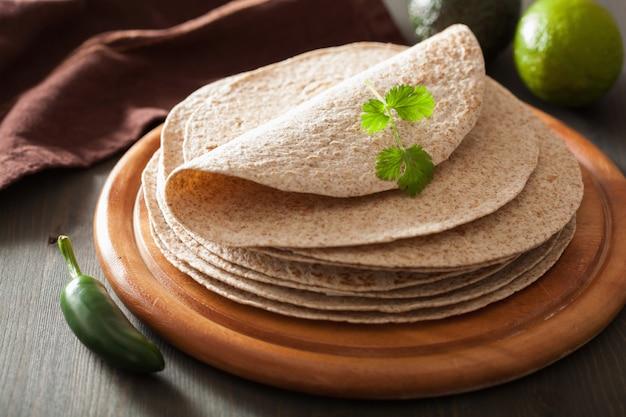 Tortillas de blé entier sur planche de bois et légumes