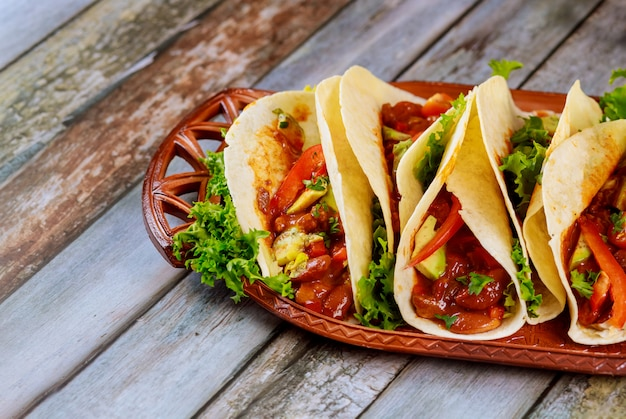 Tortillas de farine farcies de viande, de haricots et de légumes sur une table en bois