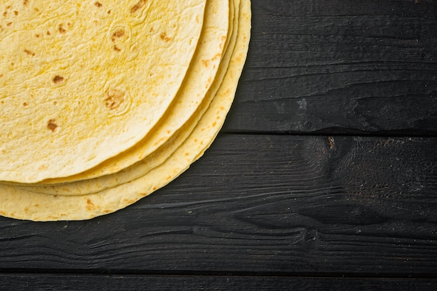 Tortillas de maïs jaune frais, sur table de table en bois noir, vue de dessus à plat