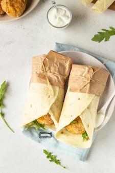 Tortillas roulées avec des côtelettes de poulet ou de dinde, de la roquette et une sauce à la crème sure.