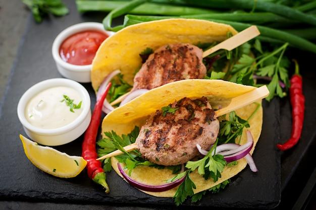 Tortillas tacos avec du kebab appétissant (boulettes de viande) et sauce sur fond noir