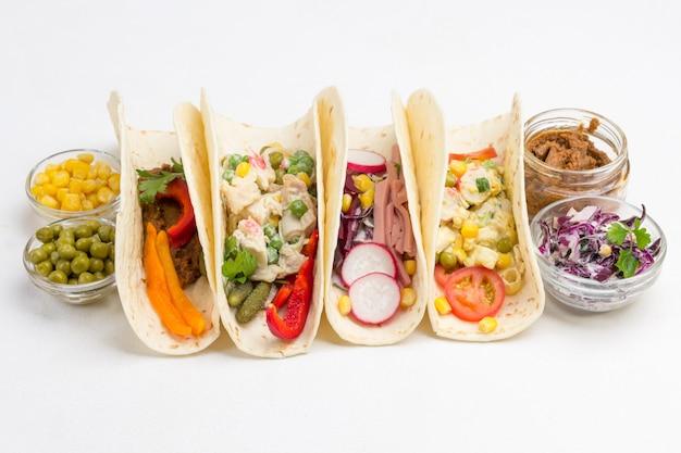 Tortillas végétaliennes avec salade végétarienne et maïs en conserve et pois verts dans des bols en verre.