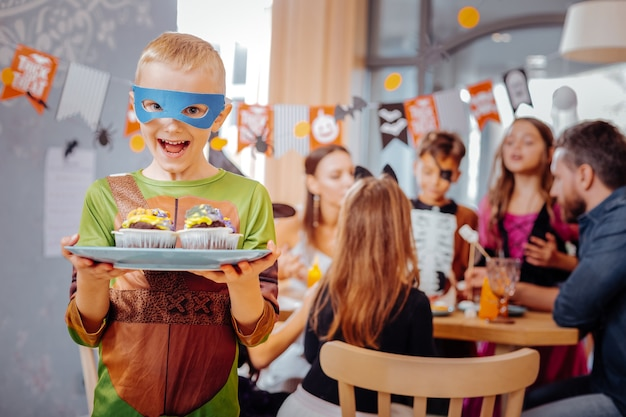 Tortue ninja. écolier aux cheveux blonds portant un costume de tortue ninja pour halloween à la recherche extrêmement joyeux et drôle