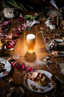 Tôt le matin après la fête, un verre de bière blonde légère et froide sur la table avec des confettis et