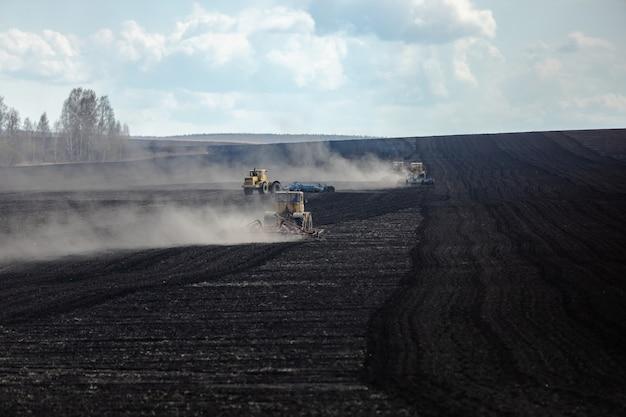 Tôt le matin, plusieurs tracteurs labourent la terre dans de grands champs