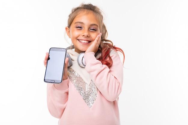 Touché petite belle fille tenant un téléphone devant ses mains et regardant la caméra, posa sa paume contre son visage contre la surface du mur orange