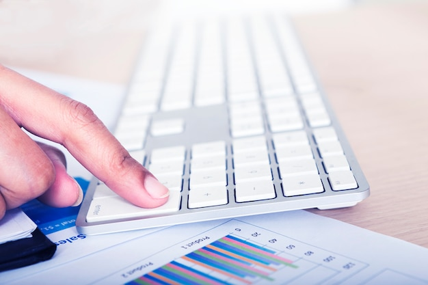 Toucher le clavier en milieu de travail d'entreprise avec des graphiques et des diagrammes.