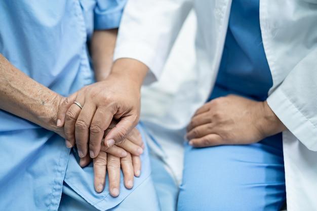 Toucher les mains patiente senior asiatique avec amour