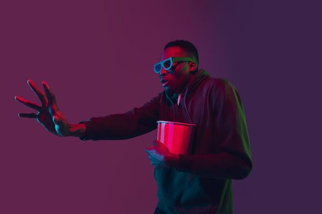 Toucher le portrait d'un homme afro-américain sur un studio dégradé à la lumière du néon