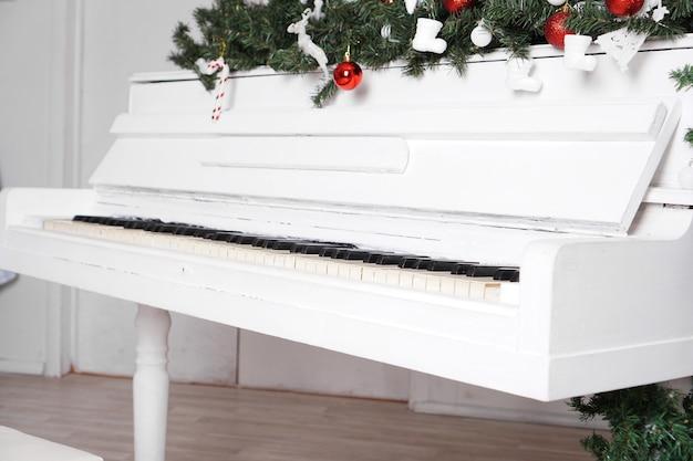 Touches sur piano droit blanc avec décor de noël avec boules rouges
