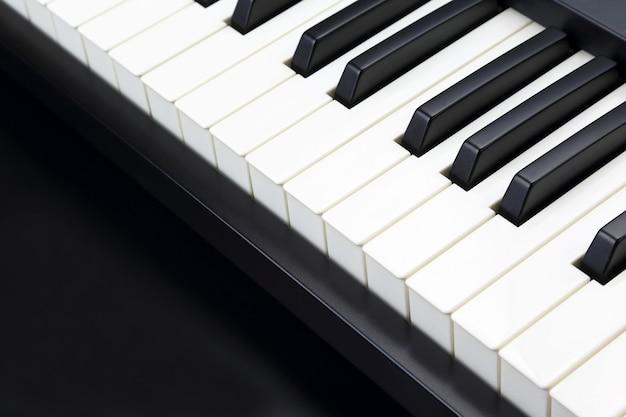 Touches de piano gros plan sur fond sombre