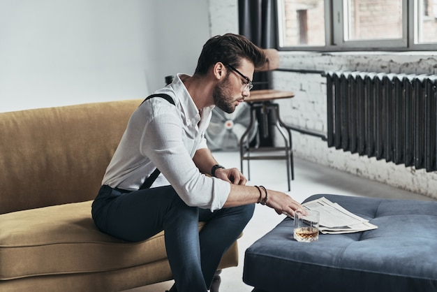 Toujours au courant des dernières nouvelles. jeune homme élégamment vêtu lisant un journal assis sur un canapé