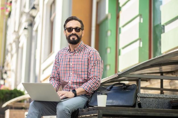 Toujours connecté. enthousiaste homme souriant assis dans la rue tout en utilisant un ordinateur portable