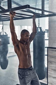 Toujours en forme. beau jeune homme africain faisant des tractions tout en faisant de l'exercice dans la salle de sport