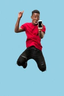 Toujours sur mobile. toute la longueur du beau jeune homme africain prenant le téléphone tout en sautant sur fond bleu studio. mobile, mouvement, mouvement, concepts commerciaux