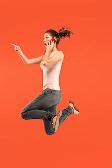 Toujours sur mobile. sur toute la longueur de la jolie jeune femme prenant le téléphone en sautant sur fond de studio rouge.