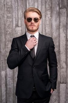 Toujours à la mode. beau jeune homme en tenue de soirée ajustant sa cravate et tenant une main dans la poche