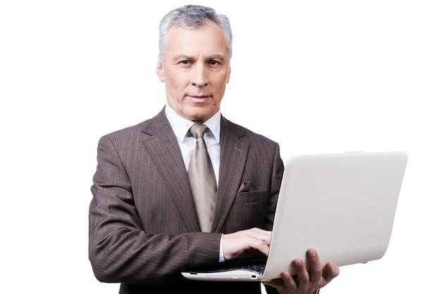Toujours occupé. bel homme mûr en tenues de soirée ajustant tenant un ordinateur portable en se tenant debout sur fond blanc
