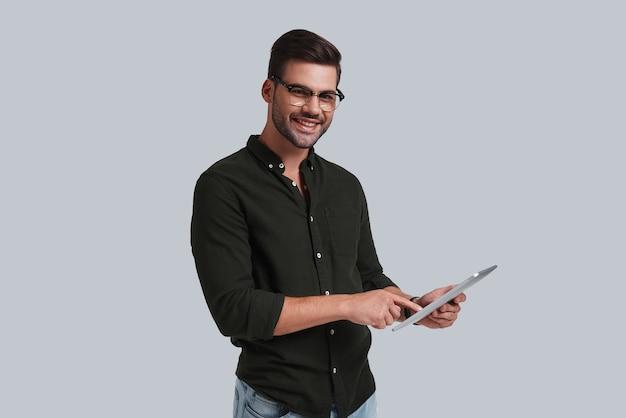 Toujours prêt à aider. beau jeune homme à lunettes tenant sa tablette numérique et regardant la caméra avec le sourire en se tenant debout sur fond gris
