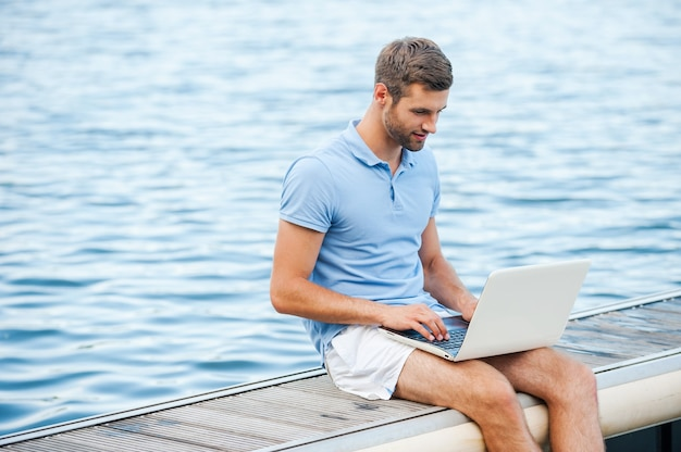 Toujours rester en contact. beau jeune homme en polo travaillant sur ordinateur portable assis sur le quai