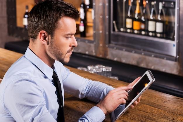 Toujours rester en contact. jeune homme confiant en chemise et cravate assis au comptoir du bar et travaillant sur une tablette numérique