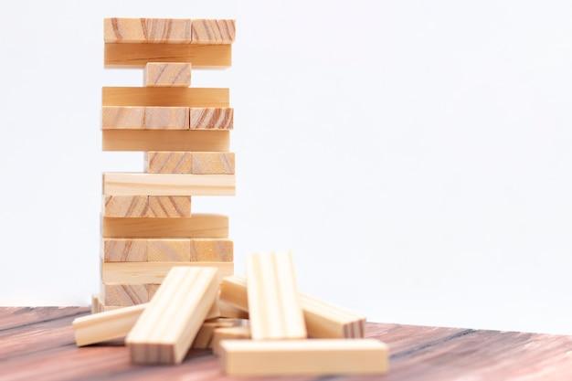 Tour en bois clair faite de blocs. jeu de société sur la table. activité de stratégie et de concentration