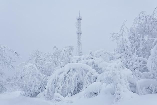 Tour cellulaire couverte de glace au-dessus d'une forêt enneigée au sommet d'une montagne contre un ciel d'hiver