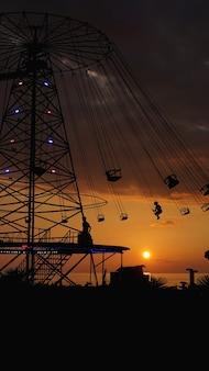 Tour de chaîne de rond-point de carrousel oscillant au coucher du soleil. divertissement sur la plage, silhouettes de palmiers sur fond de coucher de soleil sur la mer