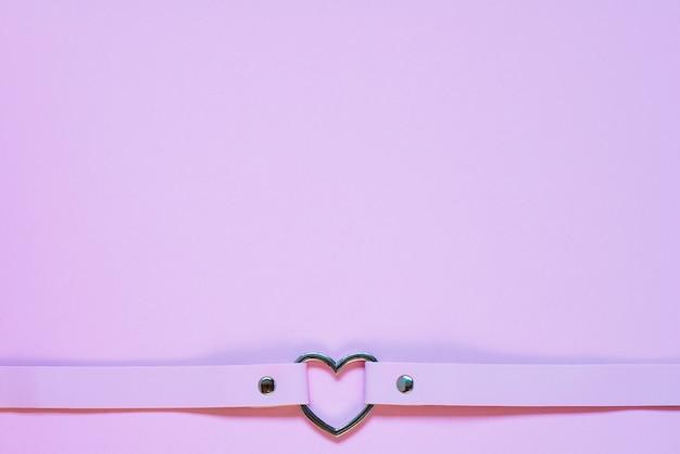 Tour de cou en cuir rose avec un coeur en métal. concept de la saint-valentin.