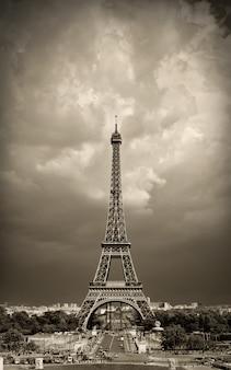 Tour eiffel à paris, france, sépia tonique contre le ciel dramatique.
