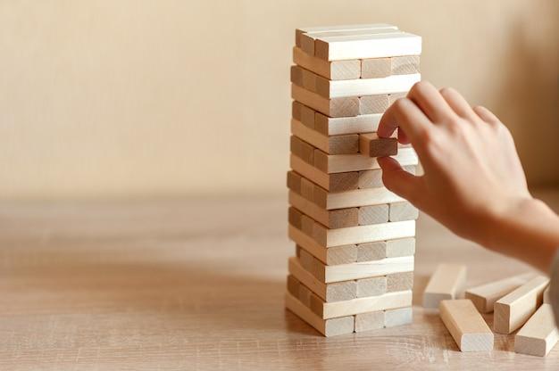 Une tour faite de blocs de bois sur un fond neutre. la main sort un bloc