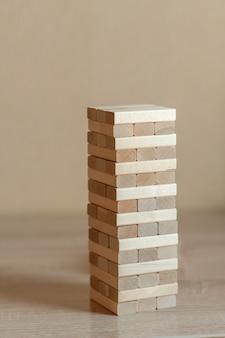 Une tour faite de blocs de bois sur un fond neutre.