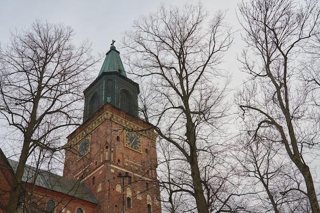 Une tour de l'horloge de la cathédrale de turku derrière les arbres en hiver.