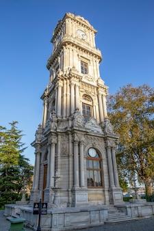 Tour de l'horloge du palais de dolmabahce avec de la verdure autour d'elle à istanbul, turquie