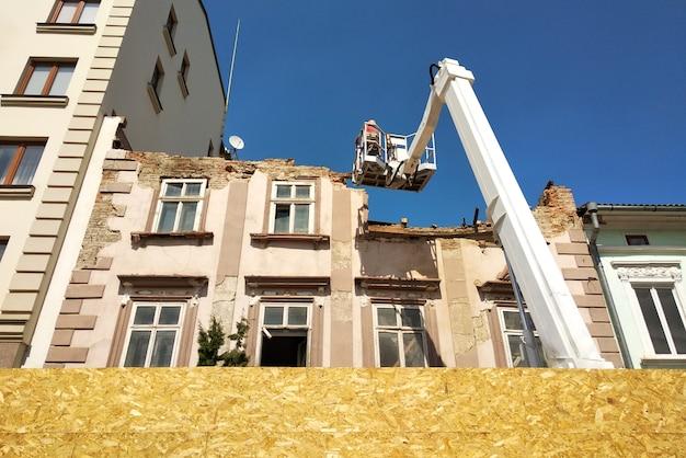 Tour de levage et vieux bâtiment en cours de démantèlement
