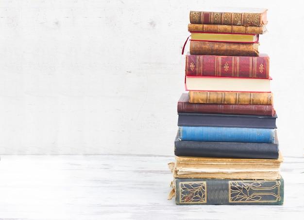 Tour de livres sur un bureau en bois blanc