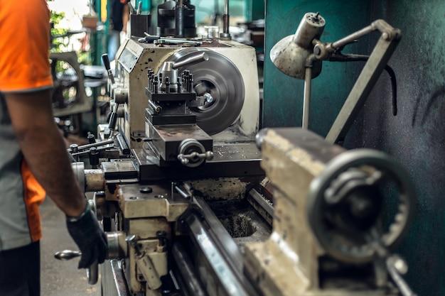 Tour machin, ouvrier en uniforme travaillant dans un tour manuel dans une usine métallurgique.