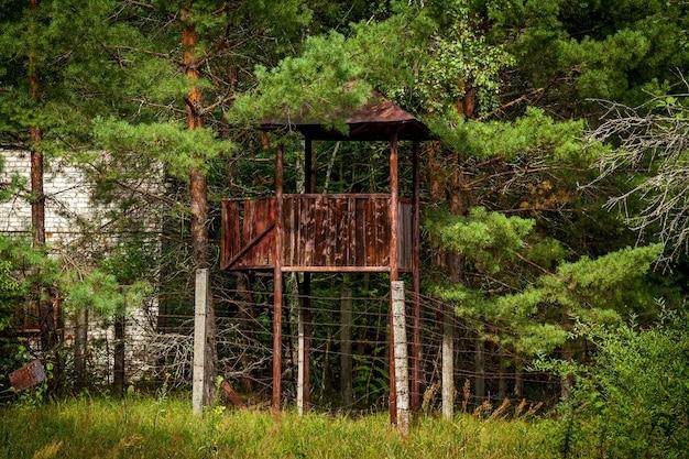 Une tour d'observation de l'ancienne unité militaire entourée d'arbres verts.