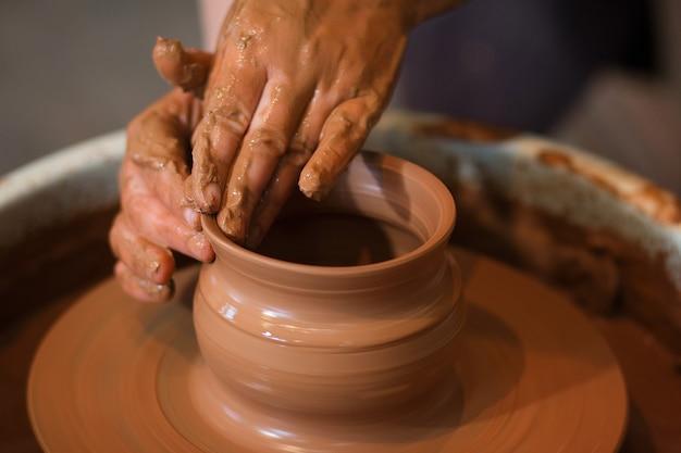 Tour de potier rotatif et poterie dessus vue de dessus un céramiste fait un pot sur un tour de potier