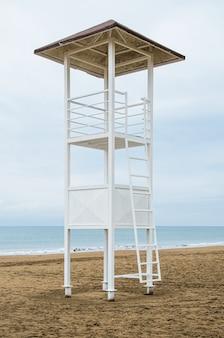 Tour de sauveteur vide et drapeau de tempête rouge sur la plage par temps nuageux. image verticale