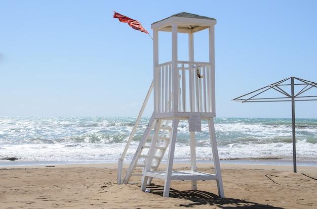 Tour de sauveteur vide et drapeau de tempête rouge sur la plage.