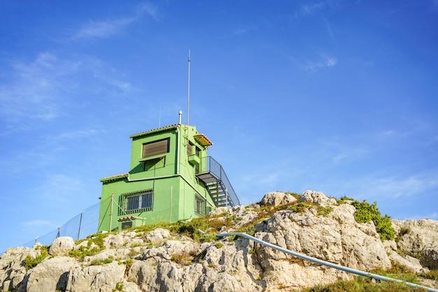 Tour de surveillance incendie verte au sommet d'une montagne à nouveau ciel bleu