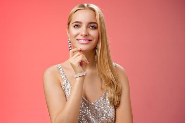Tour de taille élégant beau et riche jeune femme blonde en brillant accessoiriser argent scintillant robe élégante touche le menton ont une idée intéressante intelligente souriant curieusement, fond rouge.