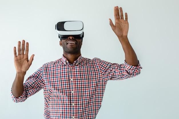 Tour de taille d'un homme afro-américain souriant joyeux testant un gadget vr en se tenant debout contre un mur blanc