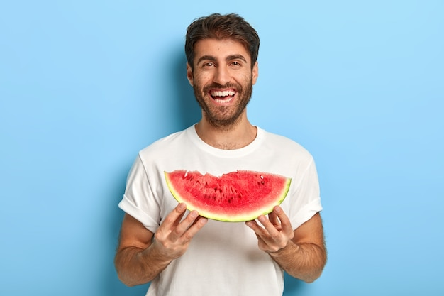 Tour de taille d'un homme souriant un jour d'été tenant une tranche de pastèque