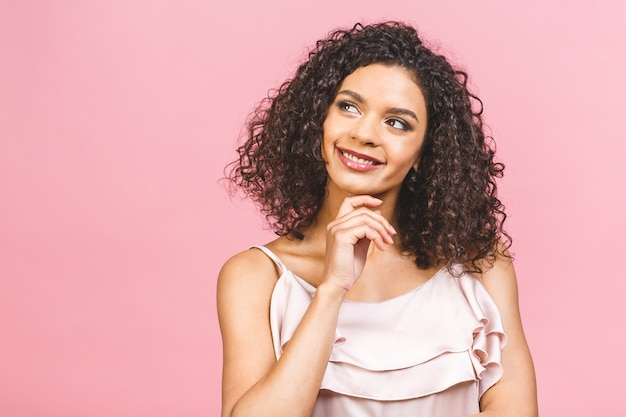 Tour de taille portrait de femme joyeuse jeune métisse aux cheveux bouclés posant en studio avec un sourire heureux. femme à la peau sombre en robe souriant joyeusement, montrant ses dents droites blanches