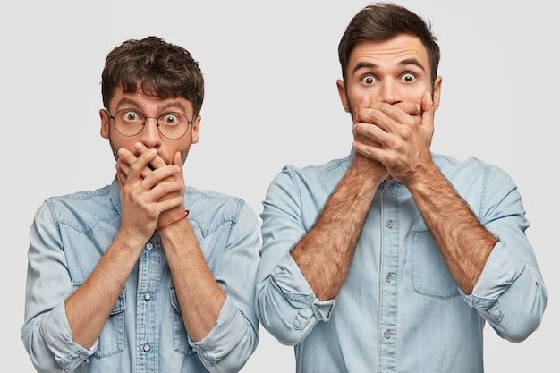 Tour de taille portrait de jeunes hommes choqués couvrir la bouche avec les deux mains, regarder avec un regard inattendu, remarquer quelque chose d'incroyable, vêtus de chemises en jean, isolé sur un mur blanc
