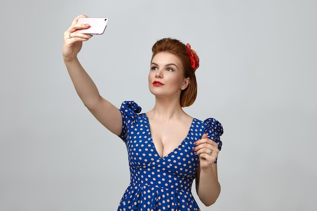 Tour de taille portrait de magnifique jeune femme à la mode habillée comme des années 1950 pin up girl holding smart phone au-dessus d'elle et prenant selfie